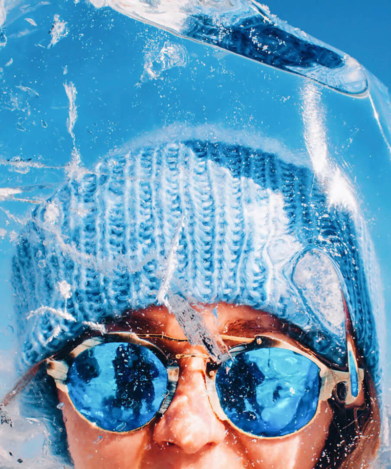 Woman with glasses looking in camera through the Baikal ice