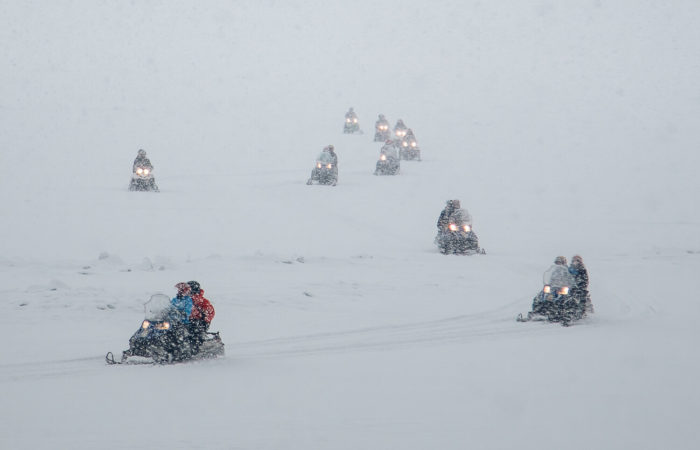 snowmobiles ride through the blizzard listvyanka