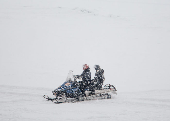 Two man riding snowmobile in blizzard